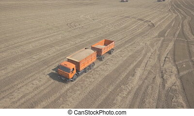 A truck with trailer loaded with wheat, traveling across...