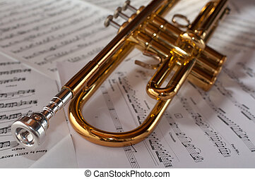 A trumpet resting on a background of music scores
