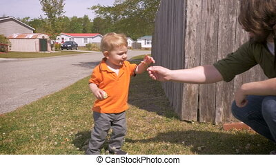 A trusting young toddler takes a flower from his father...