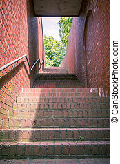 a tunnel like stairway with red bricks and handrail