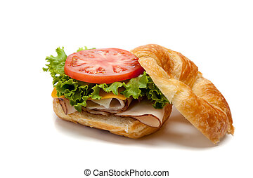 A turkey sandwich on a croissant with lettuce, cheese and...