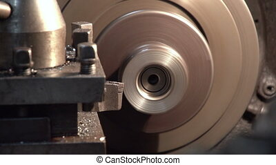 A turning ingot placed in a lathe machine and a cutting...