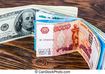 a two bunches of russian rubl and us dollar banknotes standing on brown wood surface close-up with selective focus
