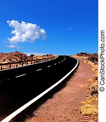 a two lane empty road curving to the horizon in a rugged desert landscape with blue cloudy sky