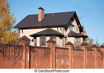 A two-storey red-brick cottage with a fence