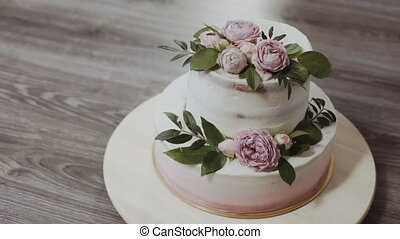 A two-tiered wedding cake, decorated with twigs of greenery and fresh flowers with roses and peonies, stands on a wooden table