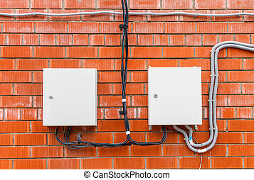 A two white box with an electric high-voltage cable on a red brick wall.