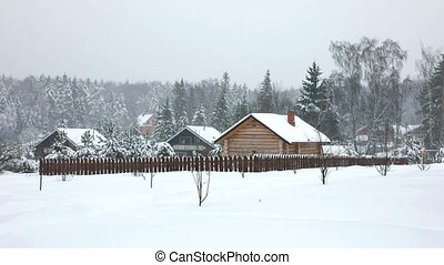 A typical Russian village in the cold winter. A log-built...