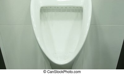 A Uinal in Men's Public Toilet - A white urinal in men's...