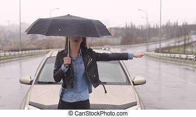 A upset girl with an umbrella catches a car standing on the road in the rain.