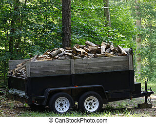 A utility trailer full of fresh cut and split hardwood for your fireplace or wood stove outside in the woods waiting to be deliverd to your house or residence.