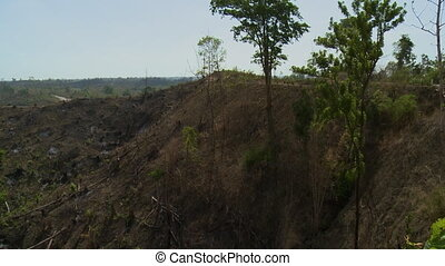 A valley with a few trees and arid land - A hand held, long...