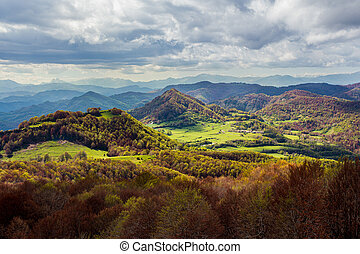 A valley with the green fields lit by the sun. Mountain peaks and heavy clouds. Catalunya, Spain