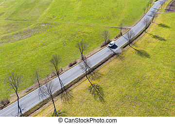 a van on an avenue from above in the sun