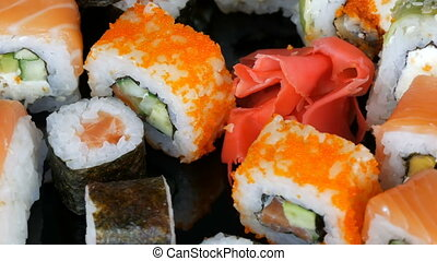 A variety of colored sushi rolls sets and ginger rotate on...