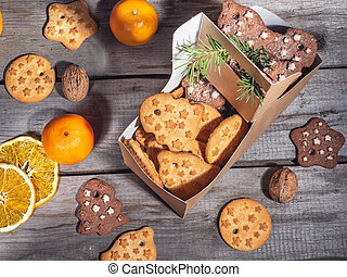 A variety of cookies in a paper bag, orange chips and tangerines lie on a wooden table.