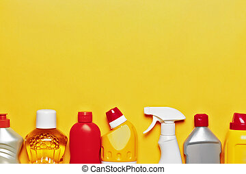 A variety of home cleaning products on a yellow background with copy space, top view