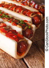 A variety of hot dogs on a table macro. vertical