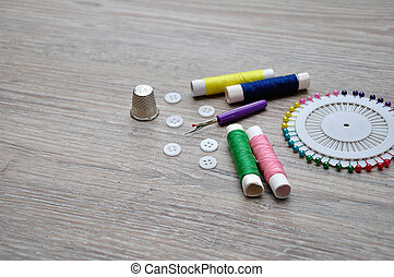 A variety of needle work supplies on a wooden background