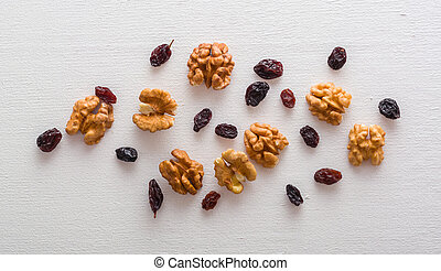 A variety of peeled walnuts and raisins on a white wooden background. View from above. Plenty of space for text.