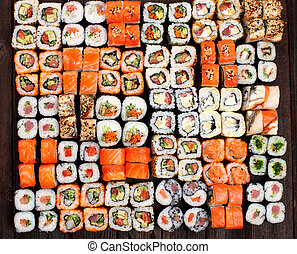 A variety of Sushi rolls on a wooden table