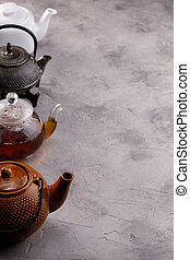 A variety of teapots with tea in a row on a gray textured ...