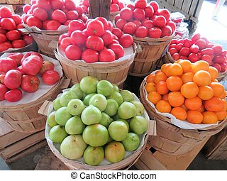 A variety of tomatoes in baskets at an outdoor farmer's market
