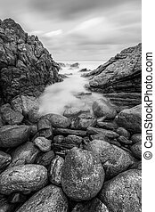 A vertical black and white sunset seascape photograph of misty waves crashing on the rocks
