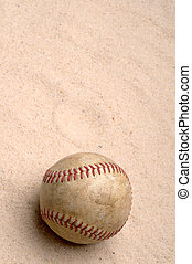 a vertical image of a baseball in the sand