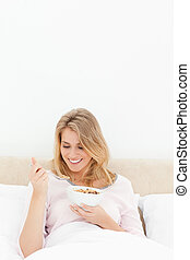 A vertical shot of a woman in bed with a bowl of cereal, as she smiles and looks at the spoon of cereal.