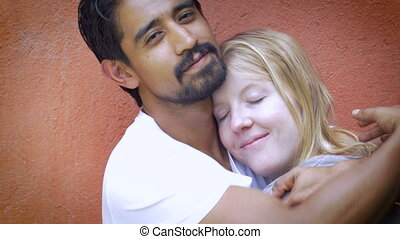 A very attractive mixed racial couple in love embracing each...