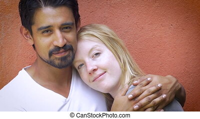 A very attractive mixed racial couple in love embracing each other and kissing