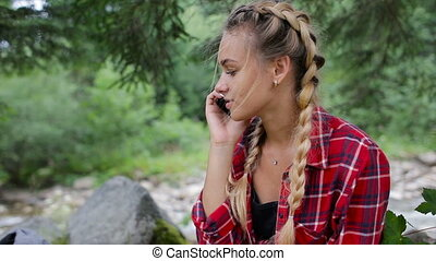 A very beautiful young girl speaks by phone in the forest