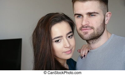 A very handsome man with blue eyes hugging his girlfriend.