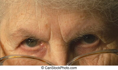 A very old woman puts on glasses and looking at the camera