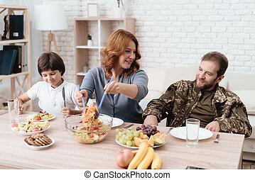 a, veteran, in, a, rollstuhl, speist, mit, seine, family., a, mann uniform, gleichfalls, sitzen, an, der, küchentisch