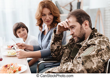 A veteran in a wheelchair dines with his family. A man in uniform is sitting at the kitchen table.