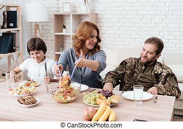A veteran in a wheelchair dines with his family. A man in uniform is sitting at the kitchen table