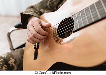 A veteran in a wheelchair is playing the guitar. Close-up photo of guitar and hands.