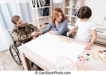 a, veteran, in, militärische uniform, in, a, rollstuhl, spends, zeit, mit, seine, family., der, junge, zieht, mit, a, brush.