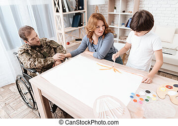 A veteran in military uniform in a wheelchair spends time with his family. The boy draws with a brush.