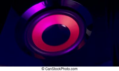 A vibrating color woofer. A big loud speaker. Color changing big woofer. Concept of musical instrument. Close up. Slow motion