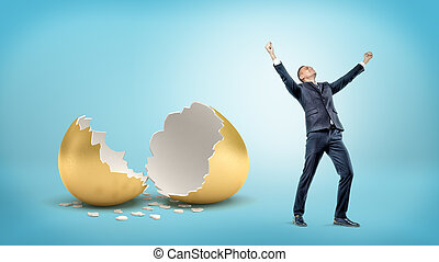 A victorious businessman stands near a large broken golden eggshell on blue background.