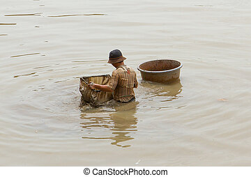 A vietnamese fisherman is searching for shells in the water