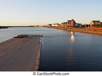 a view across the lake in southport at sunset with a jetty in front of buildings on the waterfront