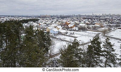 A view from a height of a small snow-covered village against the backdrop of a city and forest