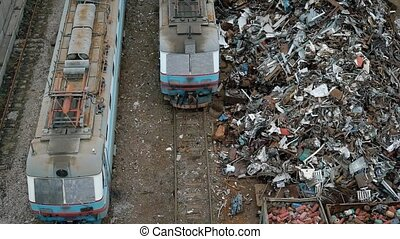 A view from above of old and broken trams, next to them is a...