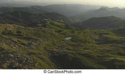 A view from above on a valley strewn with huge stones at the foot of a high cliff. A sunset panorama of the Caucasus with a turn. Review of the epic place in 4k 100mbps