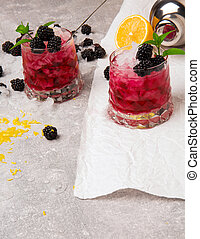 A view from above on two big glasses of cold beverages with berries and ice on gray and white background. Healthful and organic blackbrries, lemon and mint.