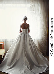 A view from behind on a stunning bride standing at the window